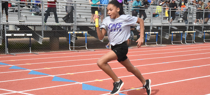 Middle School Girl Running with Baton in Track Meet