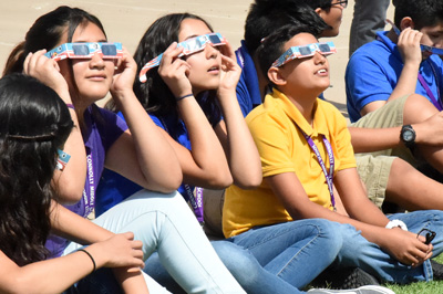 Three middle school students wearing protective eclipse shades looking up.