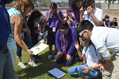 Teacher using pinhole camera to project solar eclipse on piece of white paper on grass with students looking on.