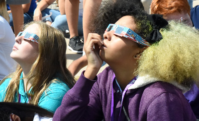 Two middle school girls wearing protective eclipse shades looking up.