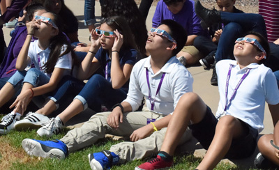 Middle school students wearing protective eclipse shades looking up.