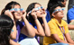 Thumbnail image of middle school students wearing protective eclipse shades looking up.