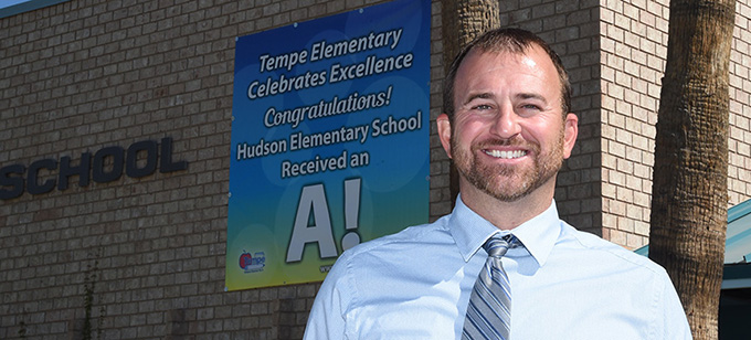 Principal Dr. Jeff Shores in front of A Banner and Congratulations Hudson Elementary School