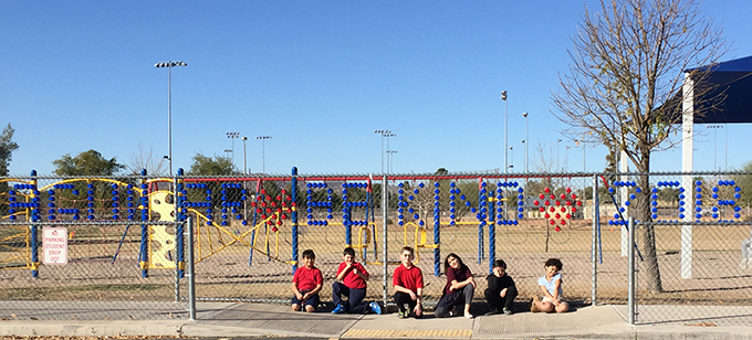Aguilar Be Kind Fence with 6 students sitting on ground