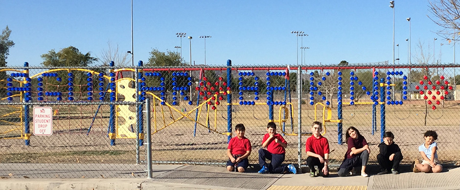 Six kids sitting in front of Aguilar Be Kind Fence