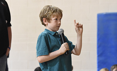 Boy holding microphone and raising hand