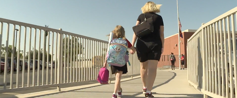Girl walking with Mom to school holding hands