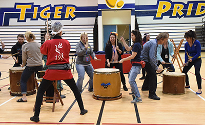 Woman instructing teachers playing Japanese drums