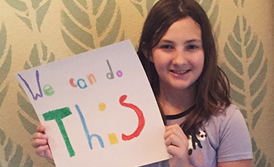 Girl Holding Sign: We Can Do This