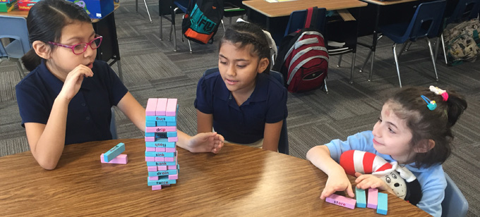 "Three young girls playing with ""jenga"" type blocks at table"