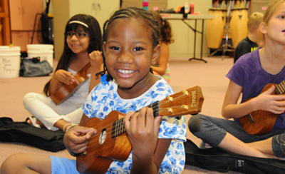 Girl smiling and playing ukele with children in background