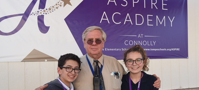 ASPIRE_Two Students with Dr Taylor standing in front of ASPIRE Academy banner