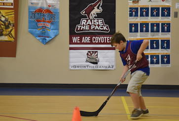 Student playing hockey in PE class