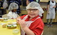 Boy with hairnet smiling at camera in red shirt