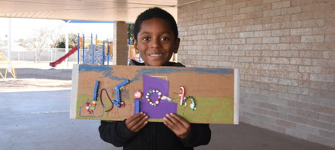 Student smiles with art project