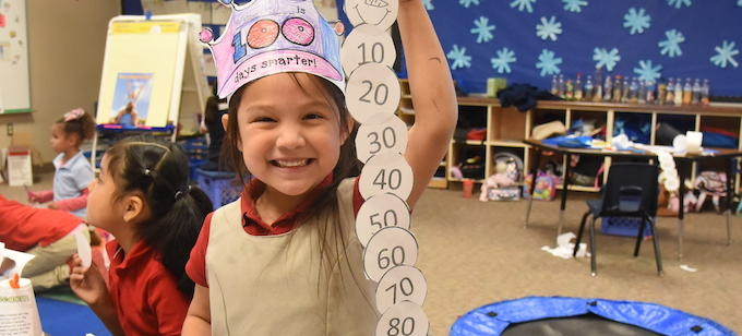 A girl in a hat that says 100 days smarter holding up a series of numbered circles. Smiling at the camera.