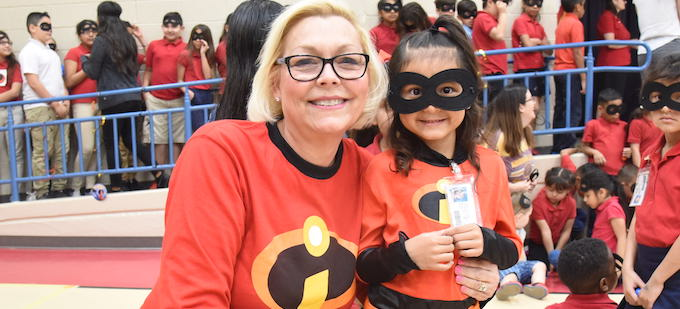 A teacher and student smiling at camera with The Incredibles outfits. The girl student is wearing a face mask.