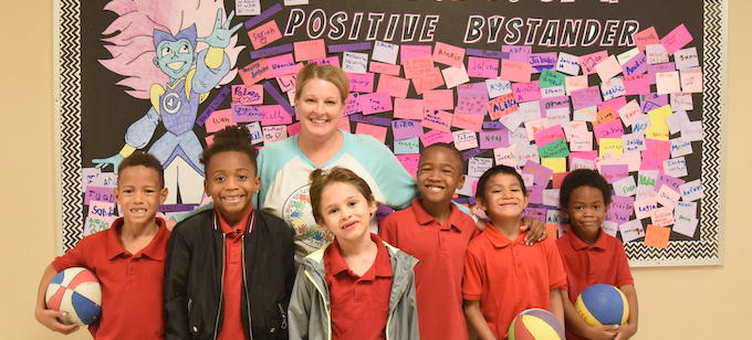 "6 students and their teacher smiling at the camera while posing in front of a decorated board that says ""Positive Bystander"""