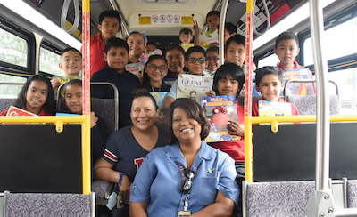 Large group shot of students on a Valley metro bus all smiling at the camera