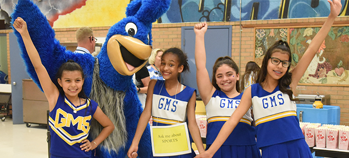 Cheerleaders smiling and posing with mascot