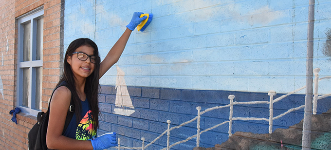 Student cleans mural on clean up day