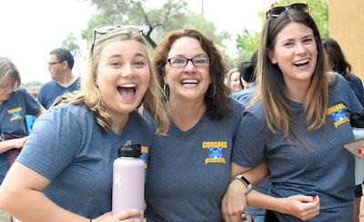 Three female teachers in same gray color t-shirt smiling at camera
