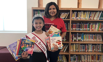 Girl with crown and sash holding books standing in front of woman in red shirt holding books in a library