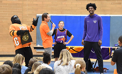 Middle school girl smiling as Suns Gorilla and Suns player and announcer look at her