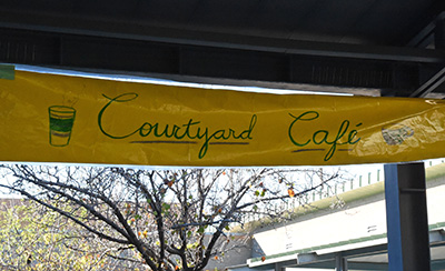 Yellow Courtyard Cafe Sign Hanging near tree