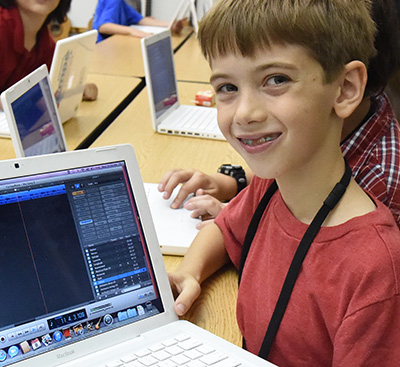 Boy smiling and showing laptop computer to camera