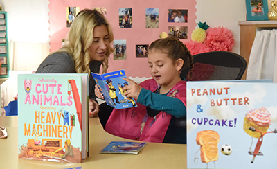 Woman looking on and smiling as girl reads book
