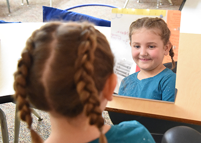 Little girl looking into a mirror at herself and her braids